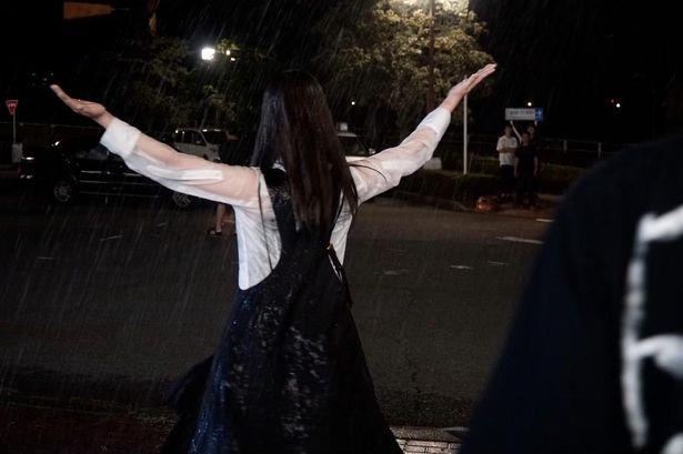 【写真を見る】両手を広げて大雨に向かう橋本の姿を収めたオフショット