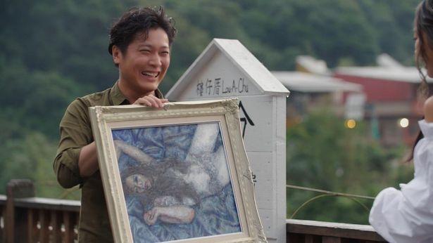 萌子さんをイメージした絵画を掲げるスギちゃん