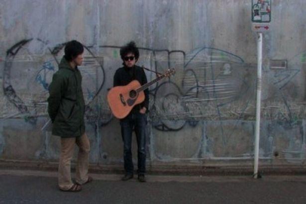 松江監督(左)は画面を自由に出入りするスタイル。作中、互いに曲や映画に込めた想いが語られる
