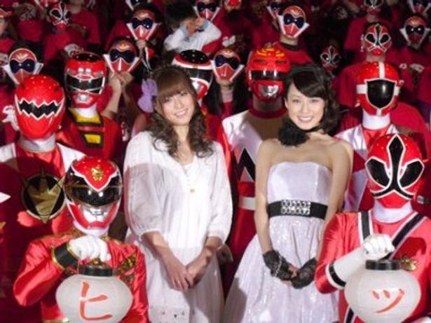 歴代ヒーローに囲まれ笑顔を見せる杉本有美と及川奈央(写真左から)