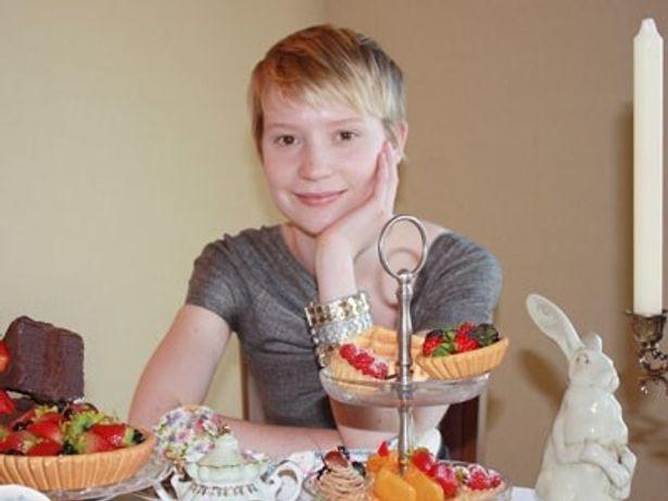 """お菓子に囲まれた""""19歳のアリス""""ことミア・ワシコウスカ。小さくなったアリスが着ているドレスが、一番のお気に入りだとか"""