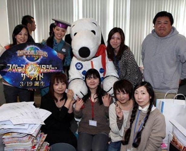 「ユニバーサル・スタジオ・ジャパン」(大阪市此花区)から宇宙服に身を包んだスヌーピーと、パークコンシェルジュが来社。編集長顔負けのアクティブさで、編集部を笑いに包んだ