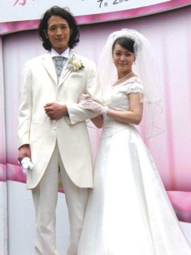 結婚式をイメージして腕を組む2人
