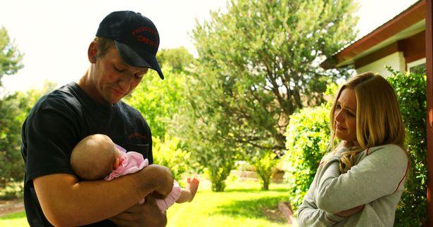 生まれたばかりの娘を抱きかかえるブレンダン