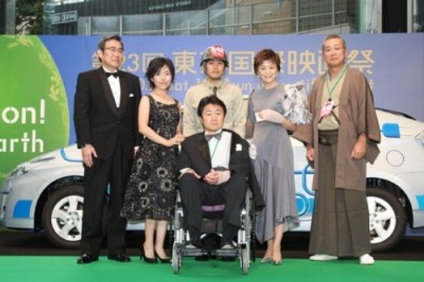 日系人兵士に車椅子を押され、すずきじゅんいち監督が登壇