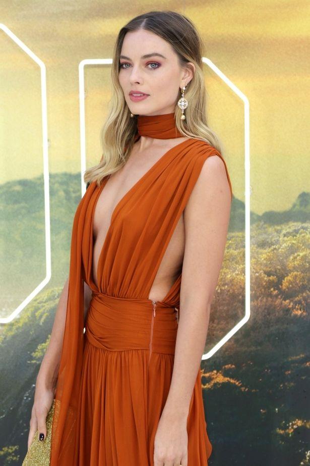 オレンジ色のシフォンドレスは谷間と脇を大胆に肌見せしたエレガントな作り