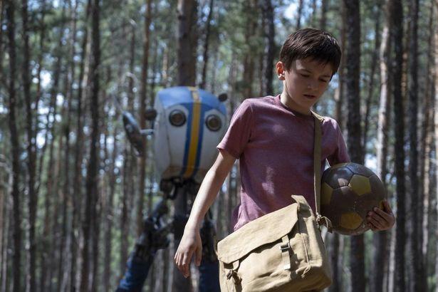 二足歩行のロボットが少年を追って歩く