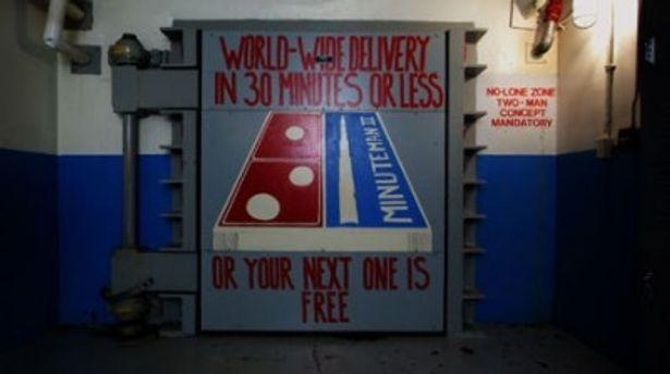"""""""世界各地に30分でお届け!届かなければ無料でもう一つ…""""とのイラストが書かれた核弾頭ミサイル発射基地の扉"""