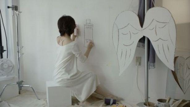 エクセレントエンリッチのボトルを壁に描く石田ゆり子
