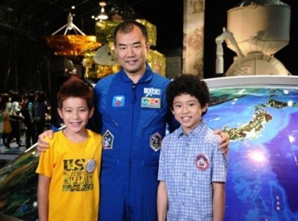 幼いムッタとヒビトの肩を抱き、彼らが憧れる宇宙飛行士として劇中に登場する野口聡一氏(中央)