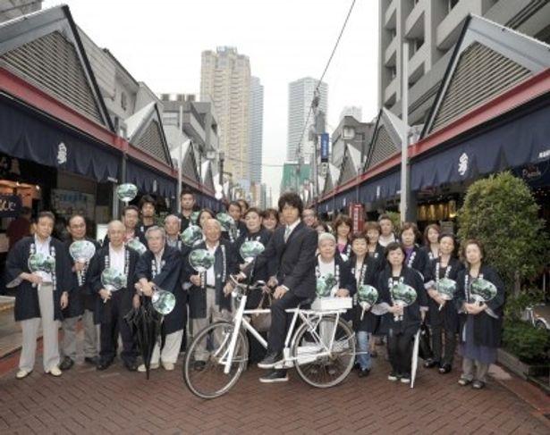 糸村の代名詞でもある自転車に乗ってポーズを決める上川隆也と月島の皆さん