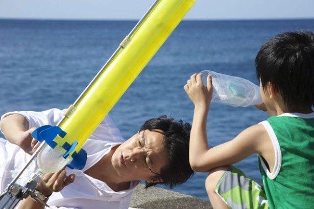 少年のために美しいといわれる海の中を見せるため、ペットボトルロケットを使った実験を繰り返す湯川