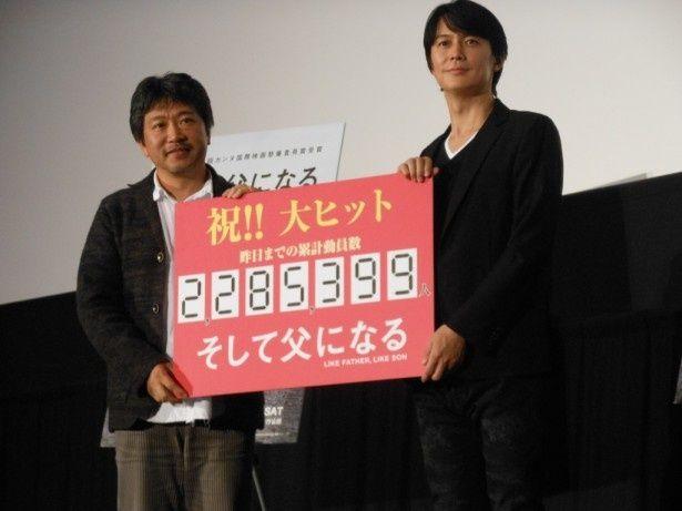 映画「そして父になる」のイベントに登場し、「累計動員数2,285,399人」と書いたフィリップを持つ主演の福山雅治(右)と是枝裕和監督(左)