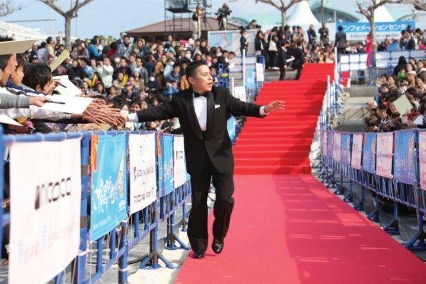 ファンの声援に応えながらレッドカーペットを歩く岡村隆史