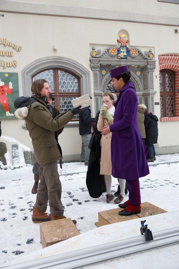雪が積もるゲルリッツの町で撮影に臨むキャストとウェス・アンダーソン監督。幻想的な雰囲気が漂う