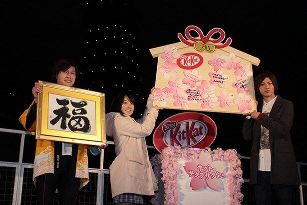 東京タワーに掛けるイメージで受験生へのメッセージが書かれた絵馬を高々と掲げる
