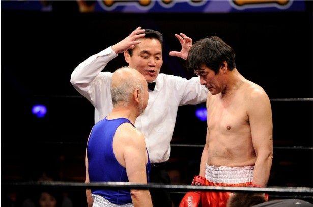 """試合直前、にらみ合う赤コーナー・""""浪速のロッキー""""赤井英和(右)と青コーナー・西口正さん(左)。中央はレフェリーのトミーズ雅"""