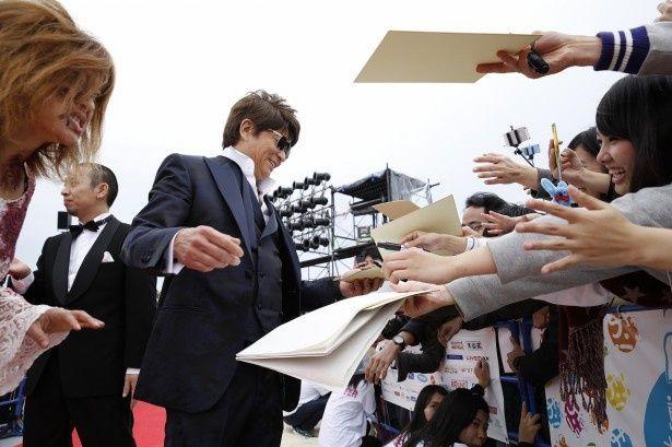 ファンにサインを求められた哀川は、笑顔で対応!