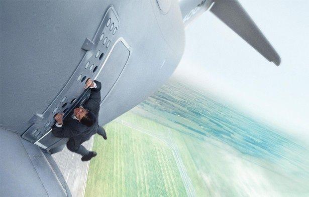 軍用機のドア外部にしがみつくイーサン・ハント(トム・クルーズ)の運命は…?(『ミッション:インポッシブル/ローグ・ネイション』)