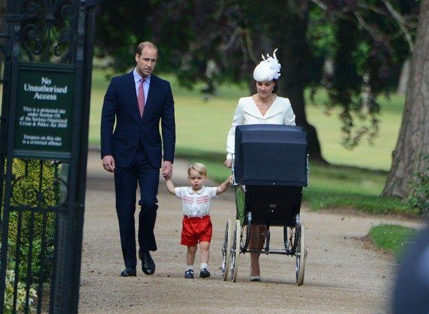 ウィリアム王子と右手をつなぎ、左手はキャサリン妃の押す乳母車をしっかり握って歩くジョージ王子