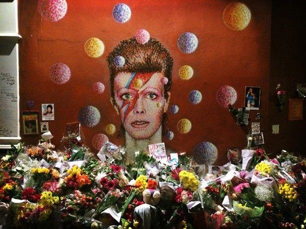 【写真を見る】ブリクストンにあるデヴィッド・ボウイの壁画の前には多くの花が手向けられている