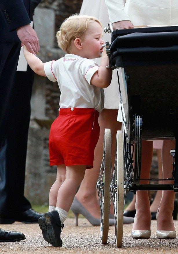 【写真を見る】背伸びをしてシャーロット王女の乳母車を覗き込むジョージ王子